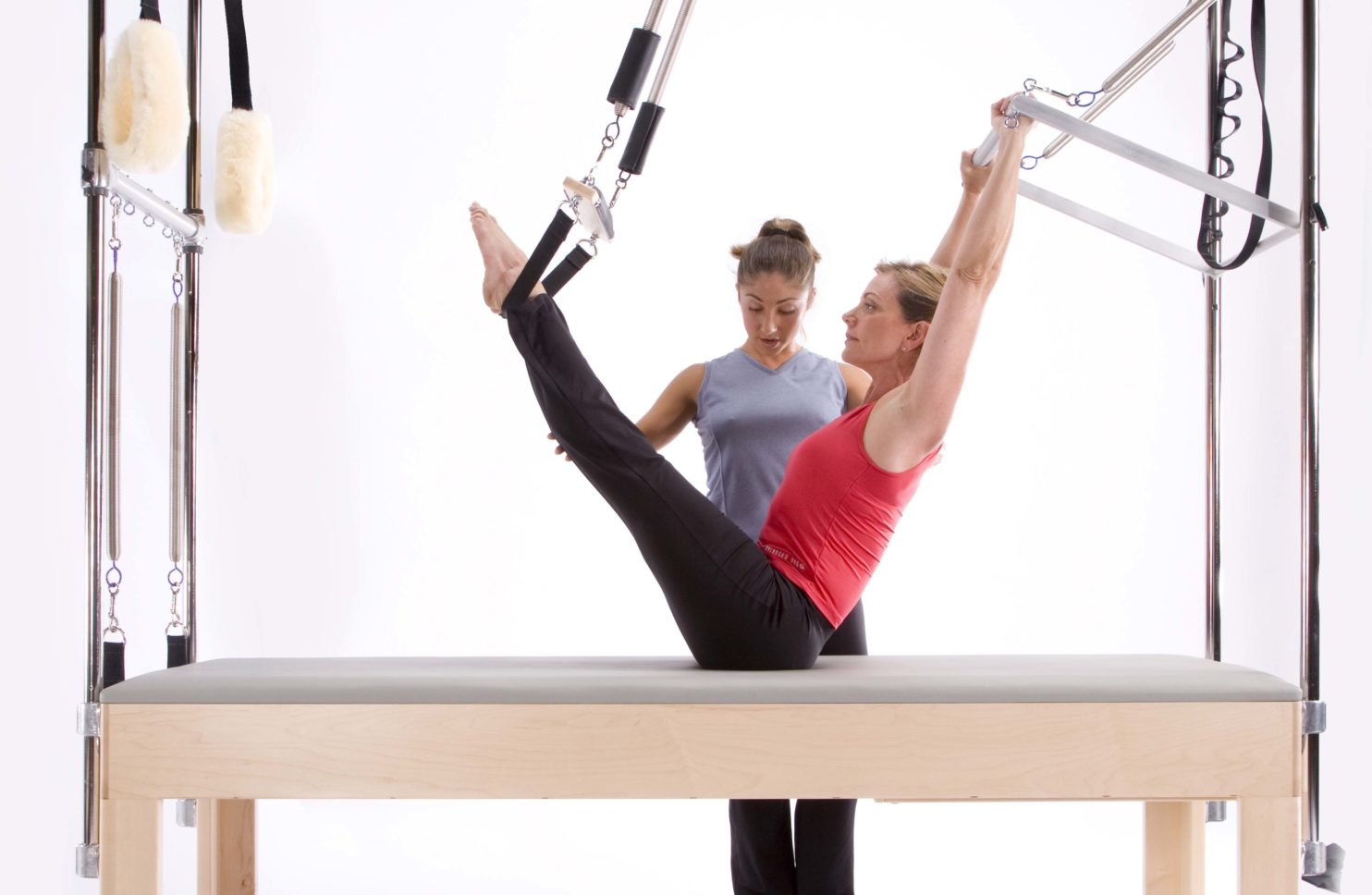 Woman doing Pilates on cadillac trapeze table