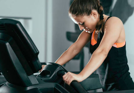 Woman on treadmill in pain from extreme exercise